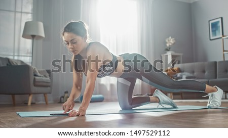 Strong Confident Fitness Girl in Grey Athletic Sportswear is Using a Stopwatch on Her Phone before Doing Push Up Workout Exercises. She is Training at Home in Her Bright Living Room with Cozy Interior #1497529112