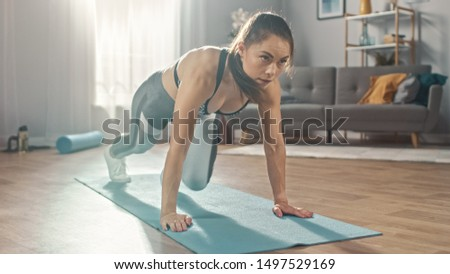 Shot of a Beautiful Confident Strong Fitness Female in a Grey Athletic Outfit is Doing Mountain Climber Exercises in Her Bright and Spacious Apartment with Cozy Minimalistic Interior. #1497529169
