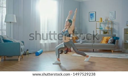 Beautiful Confident Fitness Girl in an Athletic Top is Doing Stretching Yoga Exercises in Her Bright and Spacious Living Room with Minimalistic Interior. #1497529238
