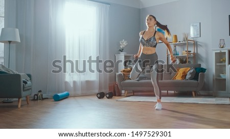 Strong and Beautiful Athletic Fitness Girl in Sportswear is Doing Cardio Exercises in Her Sunny and Spacious Living Room with Minimalistic Interior. #1497529301
