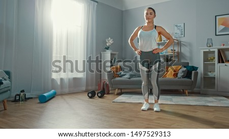 Strong and Beautiful Athletic Fitness Girl in Sportswear Prepeared for Forward Lunge Exercises in Her Bright and Spacious Apartment with Minimalistic Interior. #1497529313