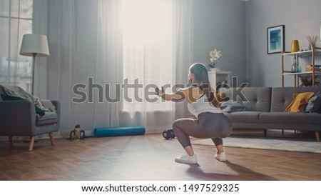 Strong and Beautiful Athletic Fitness Girl in Sportswear is Doing Squat Exercises in Her Bright and Spacious Apartment with Modern Interior. #1497529325