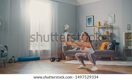 Strong and Beautiful Athletic Fitness Girl in Sportswear is Doing Squat Exercises in Her Bright and Spacious Living Room with Minimalistic Interior. #1497529334