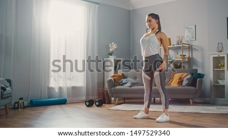 Strong and Beautiful Athletic Fitness Girl in Sportswear is Standing in Her Bright and Spacious Living Room with Minimalistic Interior. #1497529340