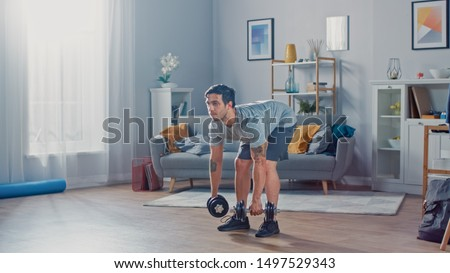 Muscular Athletic Fit Man in T-shirt and Shorts is Doing Exercises with Dumbbells at Home in His Spacious and Bright Living Room with Minimalistic Interior. #1497529343