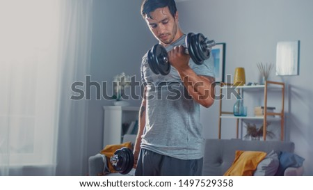 Strong Athletic Fit Man in T-shirt and Shorts is Doing Calf Raise Exercises with Dumbbells at Home in His Spacious and Bright Apartment with Minimalistic Interior. #1497529358