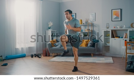 Strong Athletic Fit Man in T-shirt and Shorts is Energetically Jogging in Place at Home in His Spacious and Bright Living Room with Minimalistic Interior. #1497529361