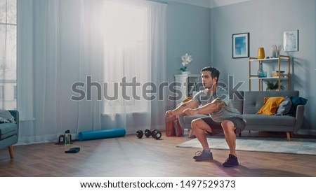 Muscular Athletic Fit Man in T-shirt and Shorts is Doing Squat Exercises at Home in His Spacious and Bright Living Room with Minimalistic Interior. #1497529373