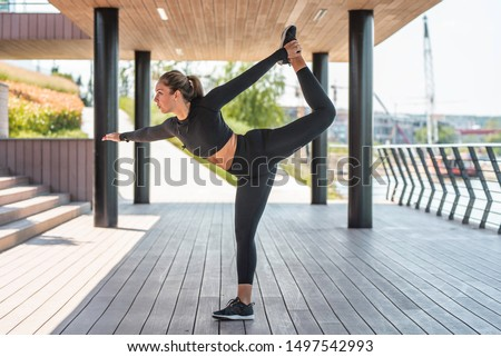 Fit athletic woman in sportswear doing workout stretching in park, near river. Girl in dark sportswear stretching her legs in shade, outdoor sport, urban fitness #1497542993