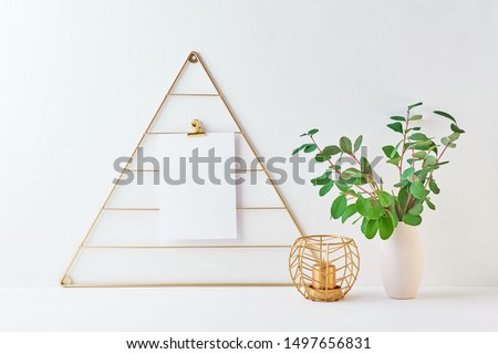 Home interior with decor elements. Mood board with empty card, branches with green leaves in a vase, interior decoration