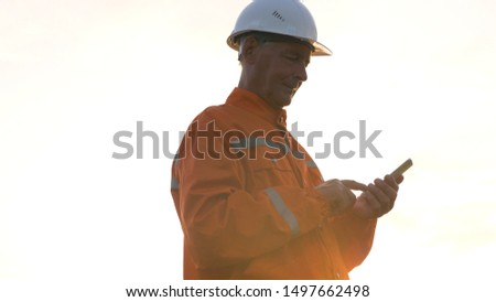 surveyor in orange jumpsuit and helmet silhouette types on modern smartphone in bright sunlight background Royalty-Free Stock Photo #1497662498