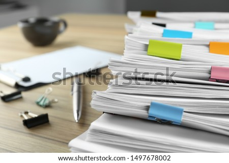 Stack of documents with binder clips and pen on wooden table, closeup view #1497678002