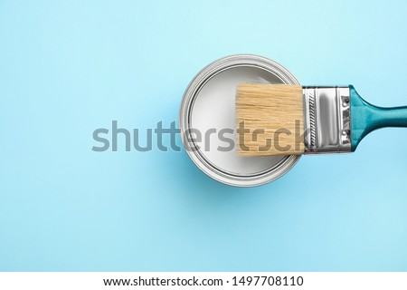 Open can with white paint and brush on blue background, top view. Space for text #1497708110