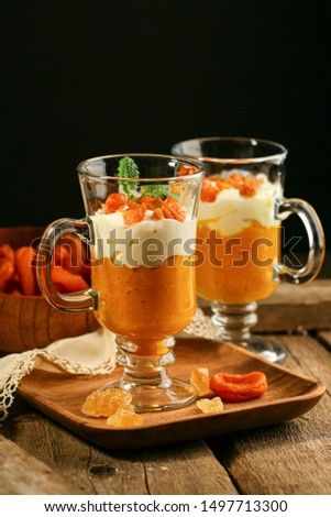 Pumpkin dessert with yogurt and dried apricots.  Homemade autumn dessert of pumpkin mousse in glass glasses on a wooden rustic table.Pumpkin keto mousse with low carbs on a dark background. The concep #1497713300