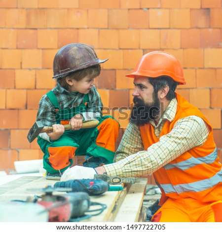 Father and son. Builders. Tools at a construction site. Hard work. Salary. Family business. Construction firm. New buildings. #1497722705