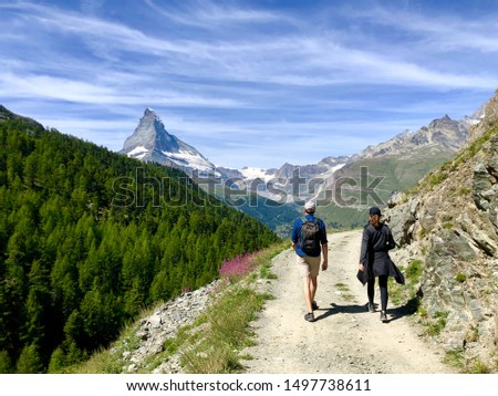 Two hiker hiking on a trail with matterhorn in the background. Young couple walking on a trail in the swiss mountains. #1497738611