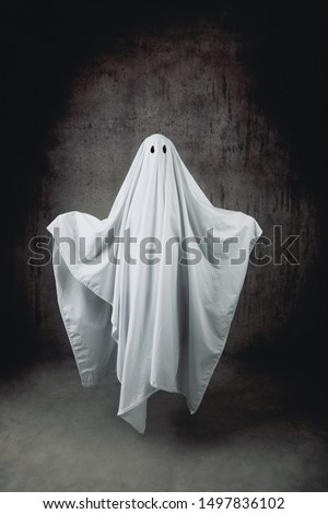 Ghost in a sheet floating in the air Royalty-Free Stock Photo #1497836102