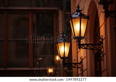 Old fashioned street lamp at night. Brightly lit street lamps at sunset. Decorative lamps. Magic lamp with a warm yellow light in the city twilight. Copy space #1497892277