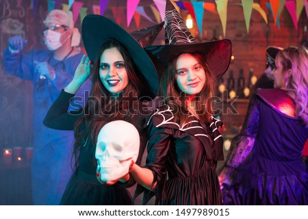Sisters dressed up like witches at a halloween party holding a skull. Witches gathering. Halloween costume. #1497989015