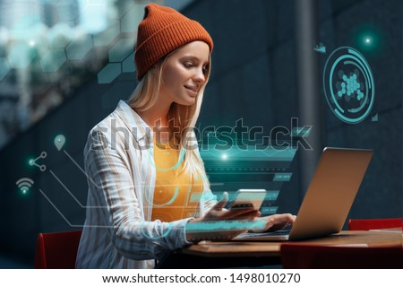 Freelancers of the future could be working with a digital HUD around them. A millennial young woman is working with her laptop and phone in a cafe, while a holographic projection encircles her. Royalty-Free Stock Photo #1498010270
