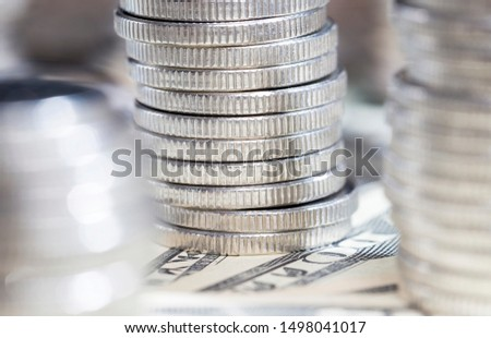 silver coins lying on paper bills of American dollars