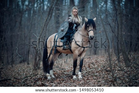 Viking warrior female ridding a horse at twilight autumn forest - Medieval movie scene #1498053410