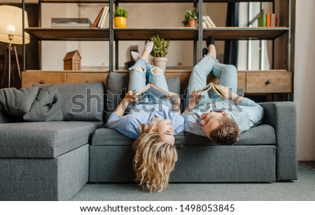Couple with books lying on the couch upside down #1498053845