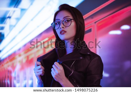 Fashion beauty shooting of gorgeous Asian model. Young beautiful woman in black jacket posing over night city dramatic red and blue neon background #1498075226