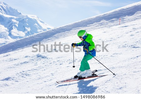 Little skier riding downhill in high mountains #1498086986