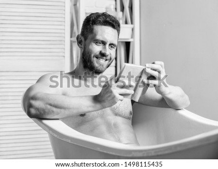 Sexy man in bathroom reading. Macho naked in bathtub. Sex and relaxation concept. man has muscular body. Wash off foam with water carefully. book lover. macho enjoying book in bath. happy man. #1498115435