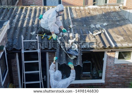 Professional asbestos removal. Men in protective suits are removing asbestos cement corrugated roofing #1498146830