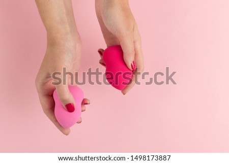 Girl hand holds a beauty makeup blender on pink background, copy space. #1498173887