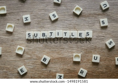 Subtitles alphabet square on wooden background.