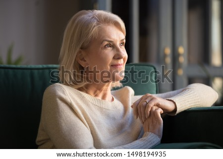 Smiling elderly woman look in distance feel cheerful positive remembering good old days, happy mature female sit on couch at home thinking, enjoying pleasant memories, recollecting or visualizing Royalty-Free Stock Photo #1498194935