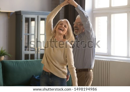 Overjoyed mature grey-haired Caucasian husband and wife have fun enjoy time together at home, happy elderly couple spouses dancing in living room, senior man lead sway smiling middle-aged woman #1498194986