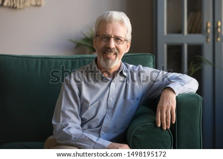 Portrait of smiling grey-haired senior man sit on couch in living room posing for picture at home, happy cheerful elderly male or grandfather wearing glasses look at camera relaxing on cozy sofa #1498195172