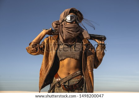 Post-apocalyptic woman with weapon outdoors. Young slim girl warrior in shabby clothes holding sword standing in a confident pose looking away. Nuclear post-apocalypse time. Life after doomsday #1498200047