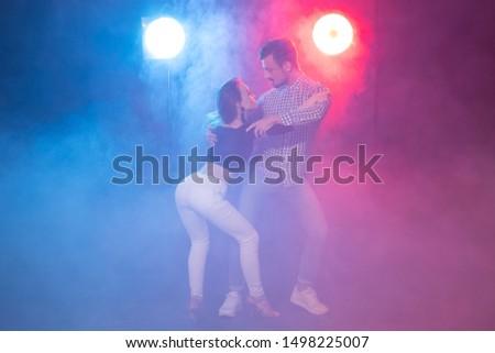 Social dance, bachata, salsa, kizomba, zouk, tango concept - Man hugs woman while dancing over lights #1498225007