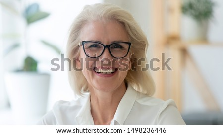 Headshot portrait of happy aged grey-haired businesswoman in glasses look at camera with toothy wide smile, close up of overjoyed senior woman boss or ceo in spectacles posing for picture