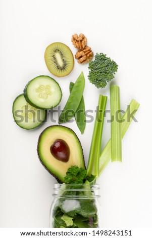 Glass jar mugs with green health vegetables lettuce leaves, lime, apple, kiwi, avocado, food concept. #1498243151