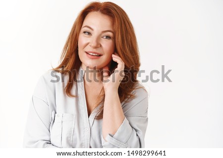 Beauty, aging, cosmetics concept. Good-looking elegant redhead mature lady touch cheek tilting head smiling amused feel fresh relieved applying anty-aging creme satisfied skin condition #1498299641