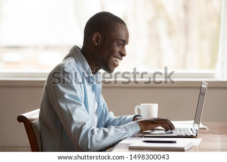 Side view of excited african American millennial man sit at table smile using laptop at home texting or messaging with friends, overjoyed biracial male type on computer, get positive response email #1498300043