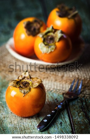 Fresh fruit Persimmons on a wooden table top. Yellow-orange kaki fruits, tropical fruits. Persimmons, kaki on the plate with a fork. Eating exotic fruits, calories and vitamins. Sweet fruits to eat. #1498338092