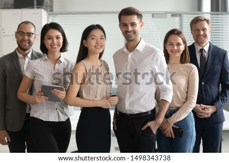 Confident young smiling diverse professional team leaders standing together with mixed race colleagues portrait. Happy group of multicultural employees posing together with skilled mentors for photo. #1498343738