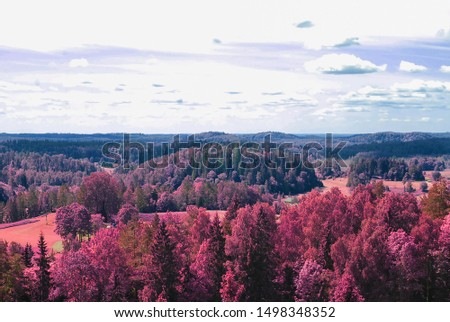 Aerial scenic view from drone with infrared camera effect of natural landscape with forest and meadows and cloudy blue sky