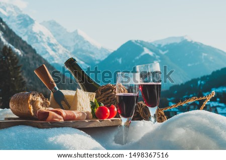 Traditional Italian food and drink outdoor in sunny winter day. Romantic alpine picnic in Dolomites with mountains background, Lambrusco cheese baguette and ham on the snow. #1498367516