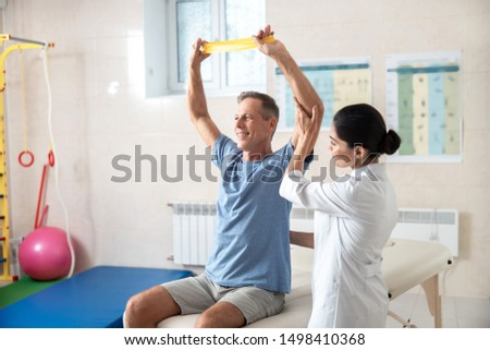 Doctor and patient in rehab room stock photo #1498410368