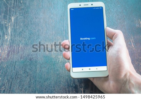 St. Petersburg, Russia, July 22 2019. White smartphone in hand on a wooden table background. Booking site on a mobile phone screen. Search engine for finding hotels around the world on the Internet.  #1498425965