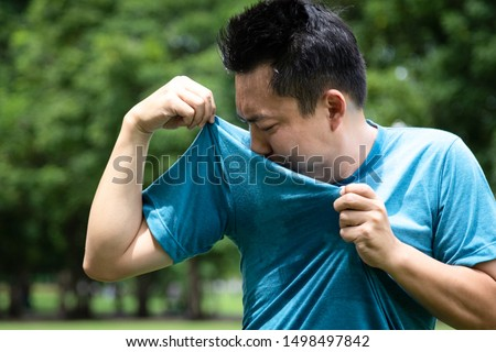 Asian young man feel bad,smelling something stinks,sniffing his wet armpit or sweating a lot because of hot weather or after exercise in outdoor park,male facial expression,concept of using deodorant #1498497842