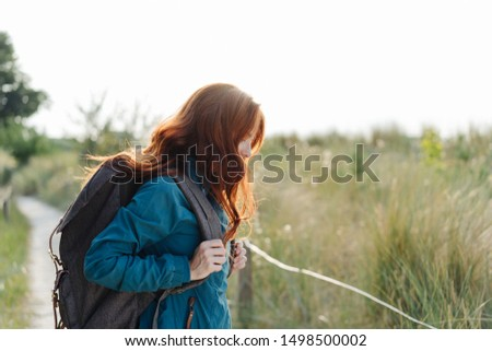 Young woman backpacker standing in profile on a wooden coastal boardwalk with her long red hair falling forwards covering her face #1498500002
